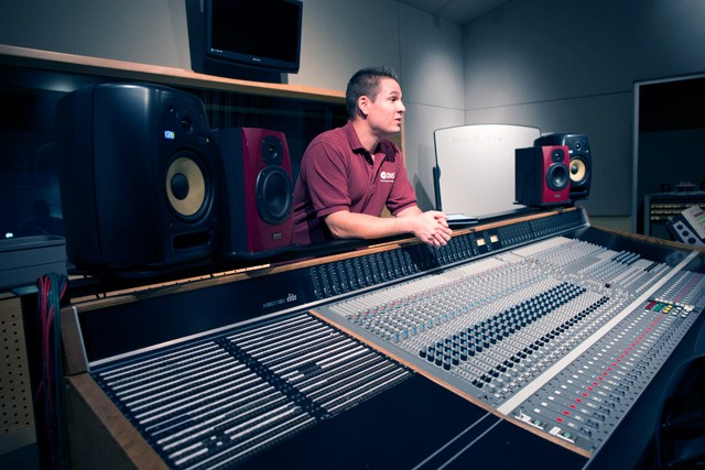 CRAS instructor stands behind the console in Studio B at CRAS Gilbert satellite campus.